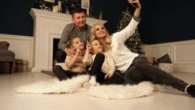 Família, feriados, tecnologia e povos - mãe de sorriso, pai e meninas que fazem o selfie com câmera sobre fotografia de stock