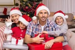 Família festiva que levanta com muitos presentes no sofá Imagem de Stock