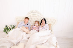 Família ficada doente, espirrar, e mentira na cama em casa Foto de Stock