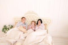 Família ficada doente, espirrar, e mentira na cama em casa Fotografia de Stock Royalty Free