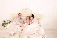 Família ficada doente, espirrar, e mentira na cama em casa Imagens de Stock Royalty Free