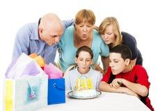 A família funde para fora velas do aniversário imagem de stock