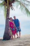 Família, geração - avó de sorriso feliz, avô e suporte pequeno perto da palma na praia foto de stock