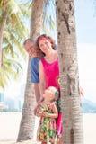 Família, geração - avó de sorriso feliz, avô e suporte pequeno perto da palma na praia imagem de stock