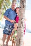 Família, geração - avó de sorriso feliz, avô e suporte pequeno perto da palma na praia fotografia de stock