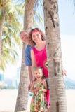 Família, geração - avó de sorriso feliz, avô e suporte pequeno perto da palma na praia imagens de stock royalty free