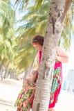 Família, geração - avó de sorriso feliz e suporte pequeno da neta perto da palma na praia foto de stock
