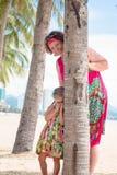 Família, geração - avó de sorriso feliz e suporte pequeno da neta perto da palma na praia imagem de stock