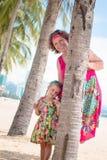 Família, geração - avó de sorriso feliz e suporte pequeno da neta perto da palma na praia imagens de stock