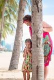 Família, geração - avó de sorriso feliz e suporte pequeno da neta perto da palma na praia fotografia de stock