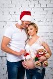 Família grávida dos jovens com um urso do chapéu de Santa do ano novo e de peluche do Natal imagem de stock royalty free