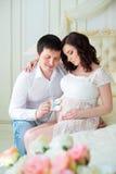 Família grávida nova feliz na expectativa do filho, guardando meninos dos montantes do bebê imagem de stock royalty free