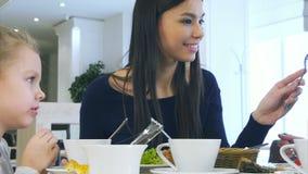 A família harmoniosa europeia tem o almoço saudável no café Eles que comem a salada vegetal, a conversa e o sorriso video estoque
