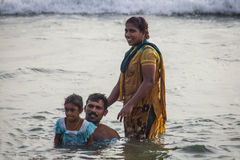 A família hindu faz santamente banha-se na afluência sagrado na praia de Papanasam Imagens de Stock
