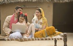 Família indiana rural que usa o portátil na cama tradicional na vila imagens de stock royalty free