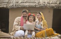 Família indiana rural que usa o portátil na cama tradicional na vila fotografia de stock royalty free