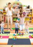 Família, infância, atividade e conceito da faculdade criadora - pais felizes e suas crianças que têm um divertimento na sala de j imagem de stock