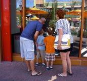 A família inspeciona a janela da loja em Disney do centro Foto de Stock Royalty Free
