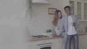 Família internacional feliz na cozinha que descansa junto Café bebendo do homem afro-americano novo, seu caucasiano vídeos de arquivo