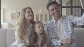 Família internacional nova bonita em casa, homem afro-americano, mulher caucasiano e menina pequena sentando-se no sofá filme