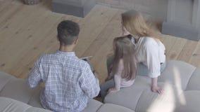 Família internacional nova feliz em casa, homem afro-americano, mulher caucasiano e menina pequena sentando-se no sofá dentro vídeos de arquivo