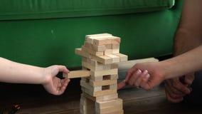 A família joga a torre de madeira A família estreitamente ligada recolhe dos blocos de madeira pequenos uma torre na estrada de f filme