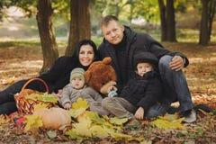 A família junto está sentando-se na manta no outono do pank Fotografia de Stock