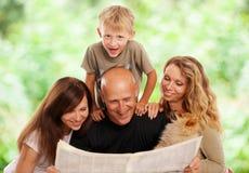 A família lê o jornal imagem de stock