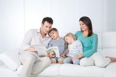 A família lê o livro Imagens de Stock Royalty Free