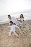 Família latino-americano com a menina que tem o divertimento na praia Fotos de Stock