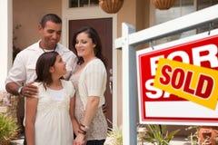 Família latino-americano na frente da HOME nova e do sinal vendido Imagens de Stock