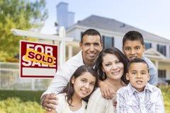 Família latino-americano na frente do sinal vendido de Real Estate, casa fotografia de stock