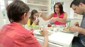 Família latino-americano que senta-se na tabela que come a refeição junto filme