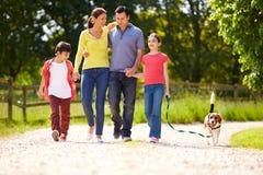 Família latino-americano que toma o cão para a caminhada