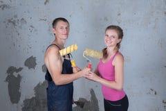 A família loving com pintura dos rolos faz reparos em um separado novo Fotografia de Stock Royalty Free