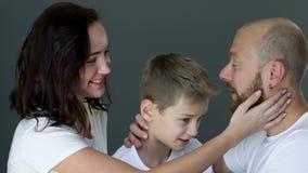 A família loving em t-shirt brancos idênticos abraça-se close-up no estúdio no photoshoot video estoque
