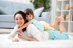 Família loving feliz A mãe bonita e pouca filha têm o divertimento, jogo na sala no assoalho, abraço, sorriso e enganam-no ao red imagens de stock