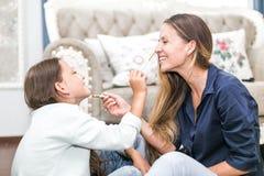 Família loving feliz A mãe e a filha estão fazendo o cabelo, tratamentos de mãos, estão fazendo sua composição e estão tendo o di imagem de stock