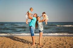 Família loving feliz nova com as crianças pequenas que têm o divertimento na praia junto perto do oceano, conceito de família fel fotografia de stock