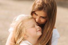 Família loving feliz Sira de mãe e sua menina da criança da filha que joga e que abraça aleia de árvores grandes Feche acima da v imagem de stock royalty free