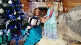 A família, mãe dá a sua filha um presente, presente do Natal, embalado belamente na caixa de papel de envolvimento com uma curva, filme