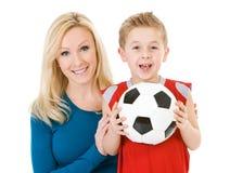 Família: A mãe está atrás do filho com bola de futebol foto de stock
