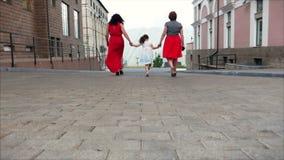 Família, mãe feliz e avó andando com a criança que guarda as mãos Conceito da família, mamã que anda no parque filme