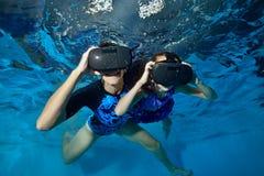A família, a mamã e o bebê felizes jogam em capacetes da realidade virtual debaixo d'água na associação Fim acima Underwater de t imagens de stock