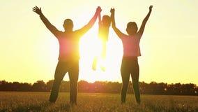 Família, mamã feliz e paizinho, jogando com uma criança fora O pai e a mãe levantam lentamente suas mãos, guardando a criança vídeos de arquivo
