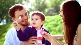 A família, a mamã, o paizinho e o filho no parque estão deixando bolhas No verão na grama verde vídeos de arquivo