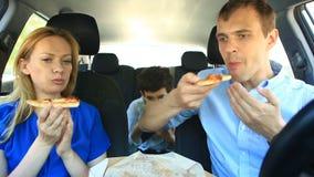 Família, mamã, paizinho e filho comendo a pizza no carro video estoque