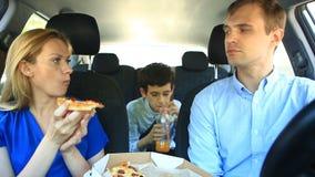 Família, mamã, paizinho e filho comendo a pizza no carro filme
