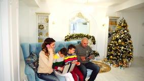 A família moderna e móvel, dois filhos e o marido e a esposa são ocupados com seus próprios casos e usam dispositivos para vídeos de arquivo