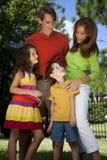 Família moderna que tem o divertimento em um parque Imagens de Stock Royalty Free